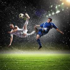 Фотообои Two Football Players In Jump To Strike The Ball At The Stadium